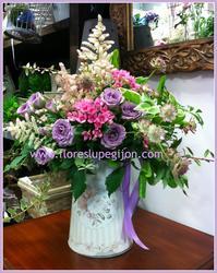Centro hecho en una regadera, con astilbe, rosas de pitiminí, astrantia y bouvardia